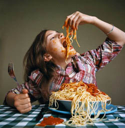 Girl eating spaghetti at table